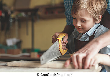 Little boy sawing a plank