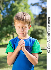 Little boy saying his prayers on a sunny day