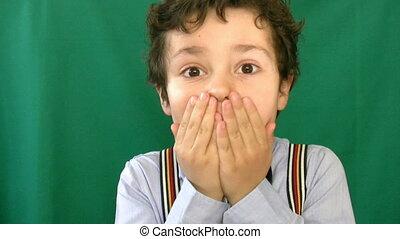 Little boy screaming in front of a green screen