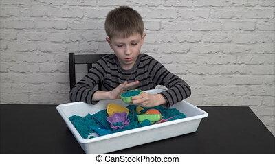 Little boy sculpting sand figures at home