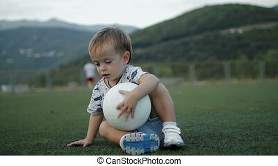 Little boy seat on the football field with ball