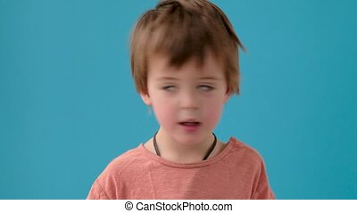 Little boy shakes head in disbelief at bright turquoise wall