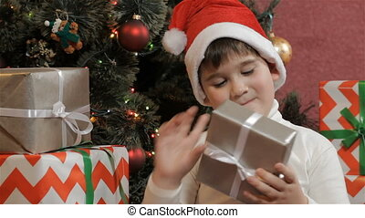 Little boy shakes the christmas gift box - Caucasian little...
