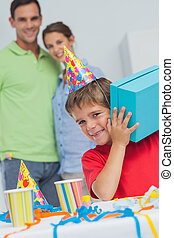Little boy shaking his birthday gift during his birthday party