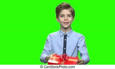 Little boy shaking red gift box.