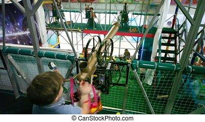 Little boy shoots from an air gun balls in playroom, indoor.