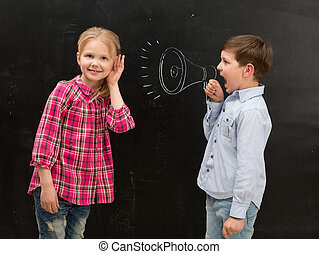 little boy shouting in drawn mouthpiece and girl covering ears with her hands