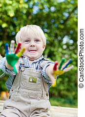 little boy showing his painted hands outside