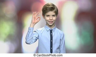 Little boy showing ok sign. Cute child in stylish shirt looking at camera. Abstract blurred background.
