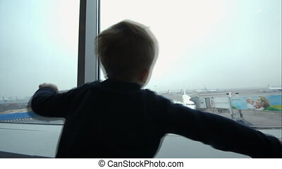 Little boy showing plane with hands looking at it out the window