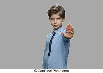 Little boy showing stop gesture on gray background.