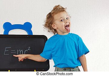 Little boy shows tongue like Einstein near formula on a ...