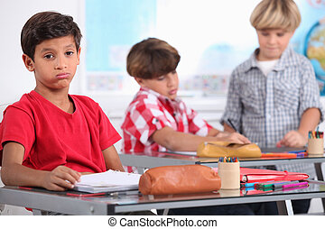 little boy sighing in a classroom