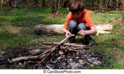 Little boy sit and drop matches to bonfire, blossom leaves...