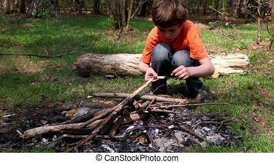 Little boy sit and drop matches to bonfire