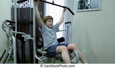 Little boy sits and hauls light weight on training equipment