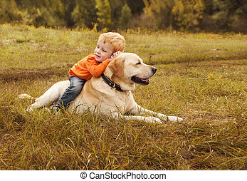 Little boy sits astride dog on walk in park. Copyspace