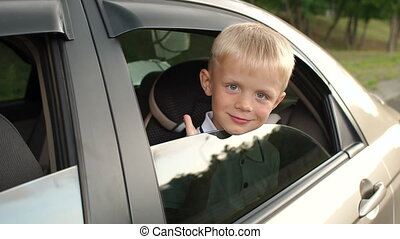 Little boy sits in the backseat of a car in a car seat, he looks out the window