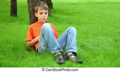 Little boy sits on grass and leans against tree at summer day