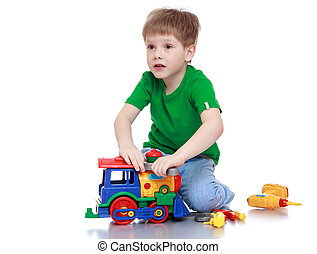little boy sits on the floor and plays with a steam locomotive