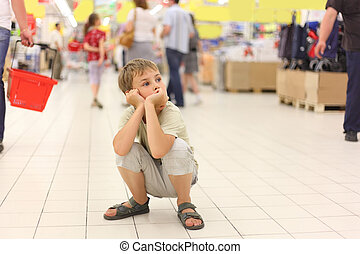 little boy sitting alone on hunkers in big store, chin on ...