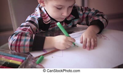 Little boy sitting at table and drawing