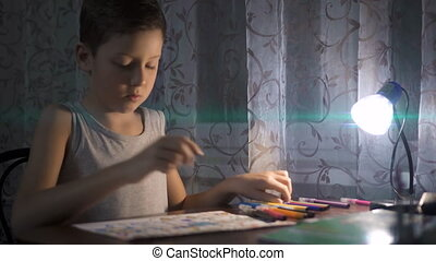 Little boy sitting at table and drawing with colored pencils in the light of a lamp