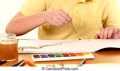 Little boy sitting at the table painting colors on white background