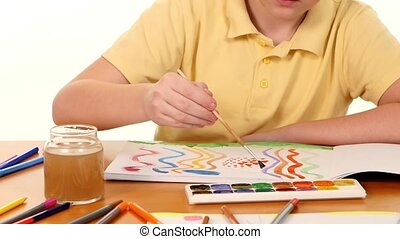 Little boy sitting at the table painting colors on white background, slow motion