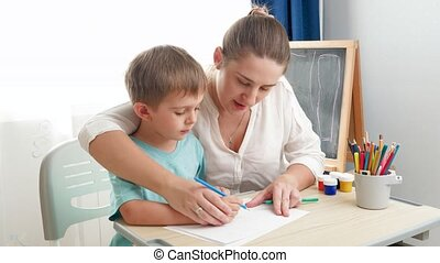 Little boy sitting behind desk at school classroom and learning drawing or writing with young woman. Concept of parenting, education and remote school at home during lockdown and self isolation
