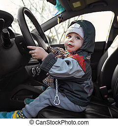 little boy sitting behind the wheel of a car