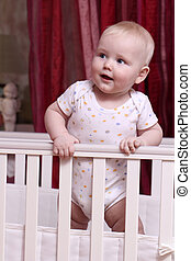 Little boy sitting in a crib