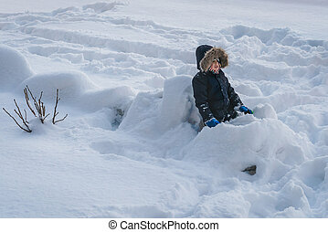 Little boy sitting in a deep snow