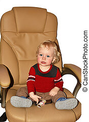 Little boy sitting in big armchair.