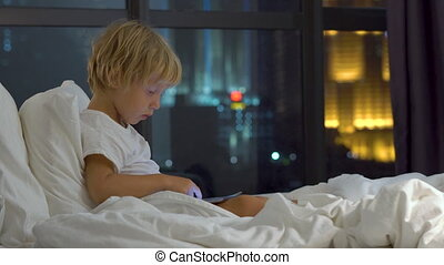 little boy sitting in his bed at night plays a tablet pc with silhouettes of a skyscraper at a background
