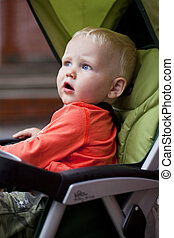 Little boy sitting in stroller