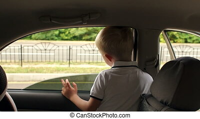 Little boy sitting in the back seat of the car, he looks out of the car window.