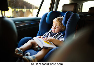 Little boy sitting in the car seat in the car, holding a book.