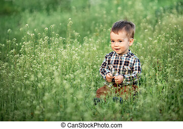 little boy sitting in the flowering meadow