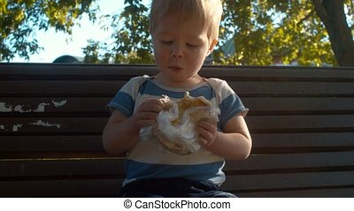 Little boy sitting on a bench and eating bun. He is glad and...