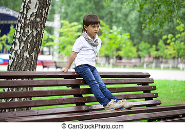 Little boy sitting on a bench in a summer park