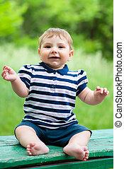 little boy sitting on a bench
