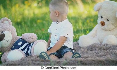 little boy sitting on a blanket with teddy bears