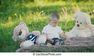 little boy sitting on a blanket with teddy bears
