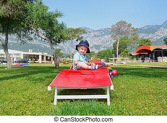 little boy sitting on a deck chair