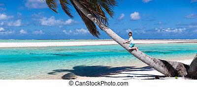 Little boy sitting on a palm tree