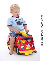 little boy sitting on a toy car