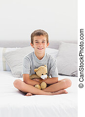 Little boy sitting on bed holding his teddy bear