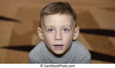 Little boy sitting on carpet sneeze