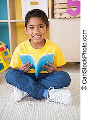 Little boy sitting on floor reading